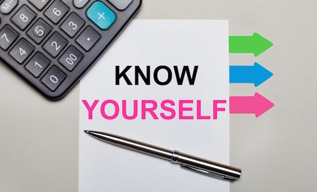 Su una superficie grigio chiaro, una calcolatrice, un foglio bianco con il testo conosci te stesso, una penna e luminosi adesivi multicolori. vista dall'alto
