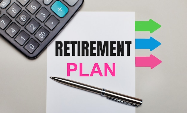Su una superficie grigio chiaro, una calcolatrice, un foglio bianco con il testo piano di pensionamento, una penna e adesivi multicolori luminosi