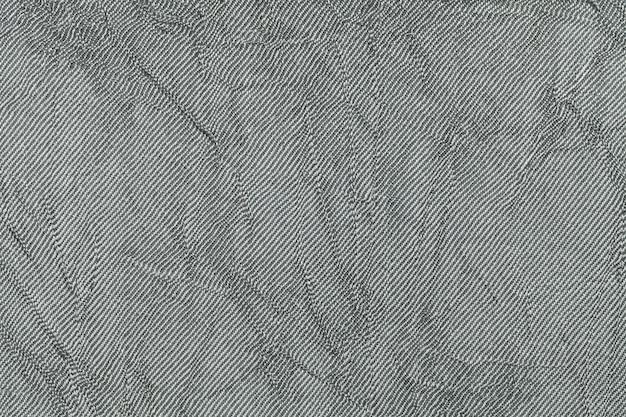 Grigio chiaro ondulato un materiale tessile. tessuto con trama naturale primo piano.