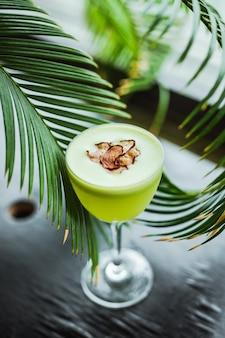Un cocktail di tequila verde chiaro in un bicchiere nick and nora, guarnito con chips di ravanello, tra le foglie di palma