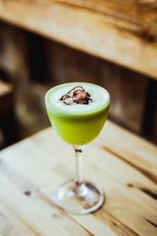 Un cocktail di tequila verde chiaro in un bicchiere nick and nora, contorno di chips di ravanello, su un tavolo di legno, angolo di 45 gradi