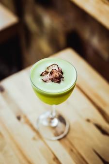 Un cocktail di tequila verde chiaro in un bicchiere nick and nora, contorno di chips di ravanello, su un tavolo di legno, angolo di 75 gradi