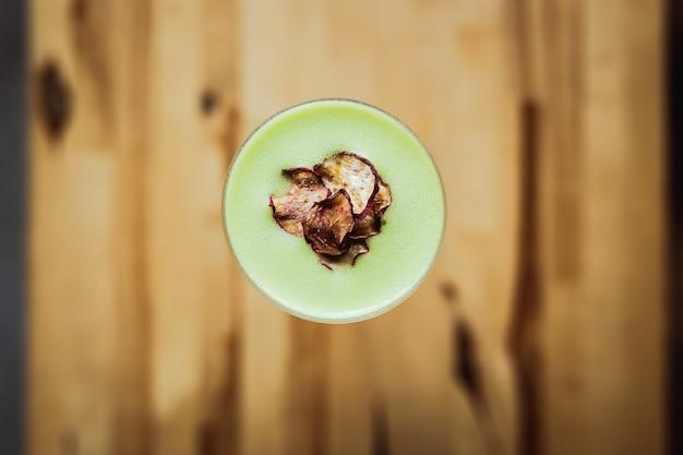 Un cocktail di tequila acida verde chiaro in un bicchiere nick and nora, contorno di chips di ravanello, su un tavolo di legno, vista dall'alto