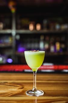 Un cocktail di tequila verde chiaro in un bicchiere nick e nora, guarnito con chips di ravanello