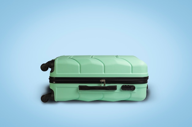 Valigia verde chiaro su ruote su sfondo blu. concetto di viaggio, viaggio di vacanza, visita di parenti