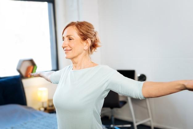 Donna matura dai capelli chiari. donna matura raggiante con i capelli legati che fa una sessione mattutina di allenamento a casa
