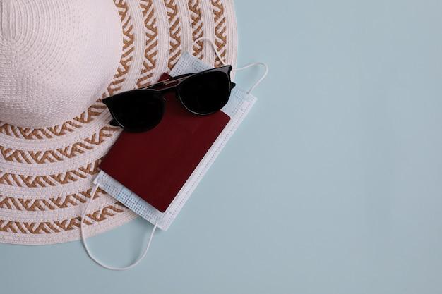Cappello leggero, passaporto, maschera protettiva e occhiali da sole sul blu