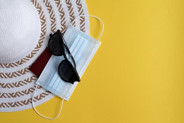 Cappello leggero, passaporto, maschera protettiva e occhiali da sole in giallo