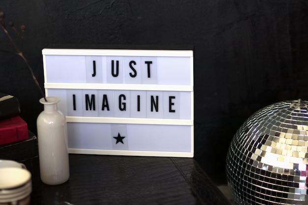 Scatola luminosa a led con caratteri tipografici, immagina solo su un tavolo in pelle con fiori e libri
