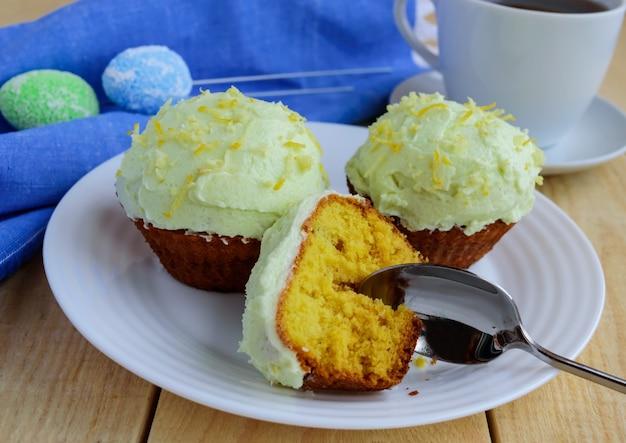 Muffin di cupcakes al limone chiaro su fondo in legno e una tazza di tè.