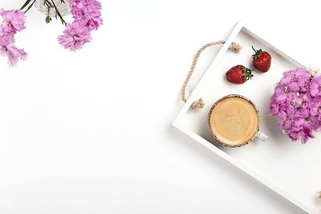 Mockup leggero per la presentazione del prodotto su un tavolo bianco con una tazza di caffè fragole e fiori...