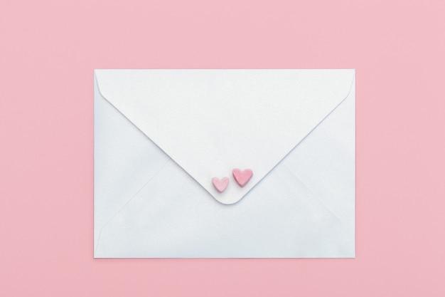 Busta artigianale in carta madreperla leggera con due cuori di marshmallow isolato su rosa