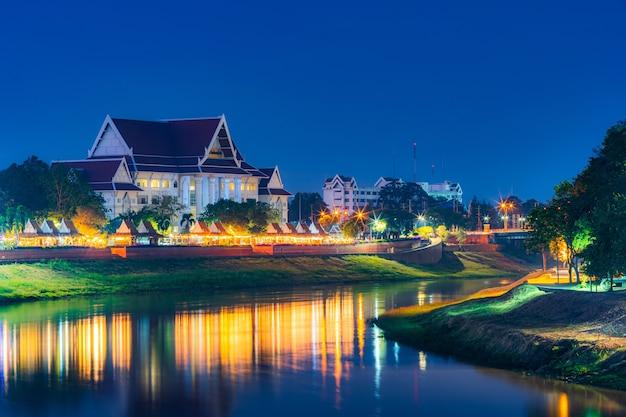 Luce sul fiume nan con corte provincia di phitsanulok edificio presso il fiume nan e il parco di notte a phitsanulok, thailandia.