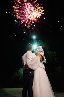 Spettacolo di fuoco notturno sullo sfondo del cielo notturno con gli sposi novelli