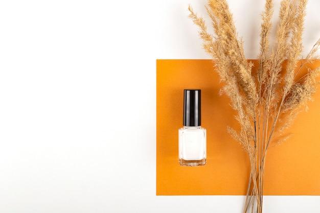 Smalto per unghie nude chiaro su superficie calda e luminosa con un bouquet di fiori secchi