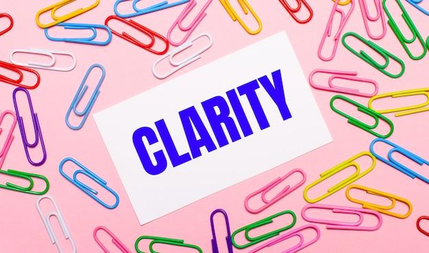 Su uno sfondo rosa chiaro, graffette colorate e luminose e una carta bianca con il testo clarity