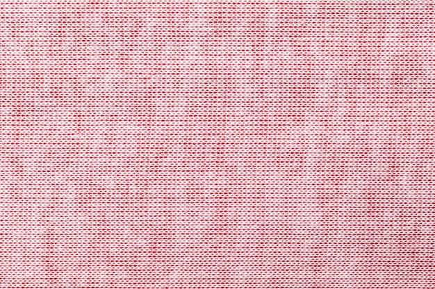 Fondo rosa-chiaro da una materia tessile con il modello di vimini, primo piano.