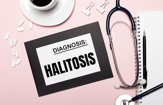 Su uno sfondo rosa chiaro, un quaderno con penna, stetoscopio, pillole bianche, graffette e un foglio di carta con la scritta halitosis. concetto medico