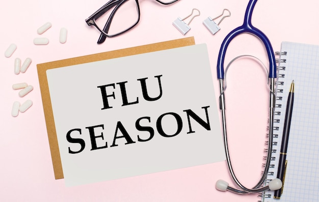 Su uno sfondo rosa chiaro, uno stetoscopio, pillole bianche e fermagli per carta, bicchieri in cornici nere e un foglio di carta con il testo flu season