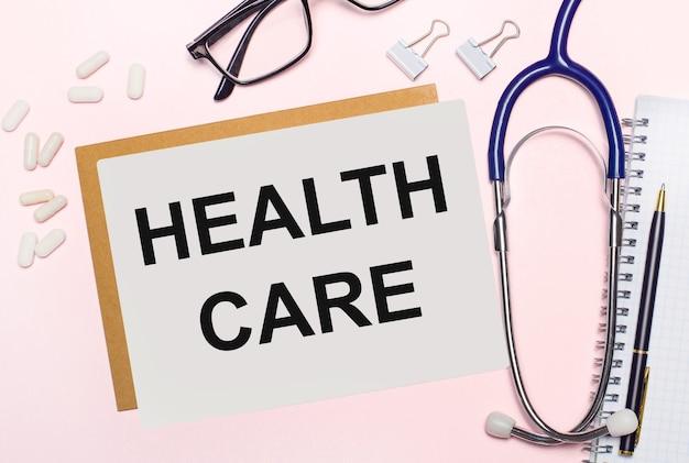 Su uno sfondo rosa chiaro, uno stetoscopio, pillole bianche e fermagli per carta, occhiali in cornici nere e un foglio di carta con il testo health care. vista dall'alto. concetto medico