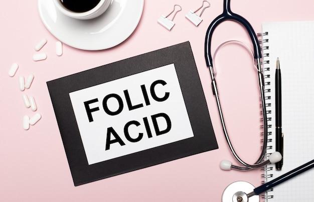 Su una superficie rosa chiaro, un taccuino con una penna, uno stetoscopio, pillole bianche, graffette e un foglio di carta con il testo acido folico