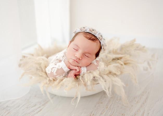 Ritratto leggero di piccola bella neonata che indossa la corona che dorme nel bacino con la decorazione della pelliccia durante il servizio fotografico dello studio. simpatico bambino che fa un pisolino tenendosi per mano e le guance