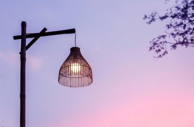 Luce sulla lampada in rattan sul momento romantico al crepuscolo