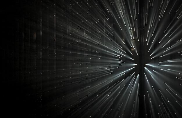 Raggi di luce attraverso piccoli fori in uno spazio buio