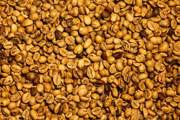 Chicchi di caffè gialli tostati chiari vista dall'alto carta da parati e struttura dei chicchi di caffè gialli
