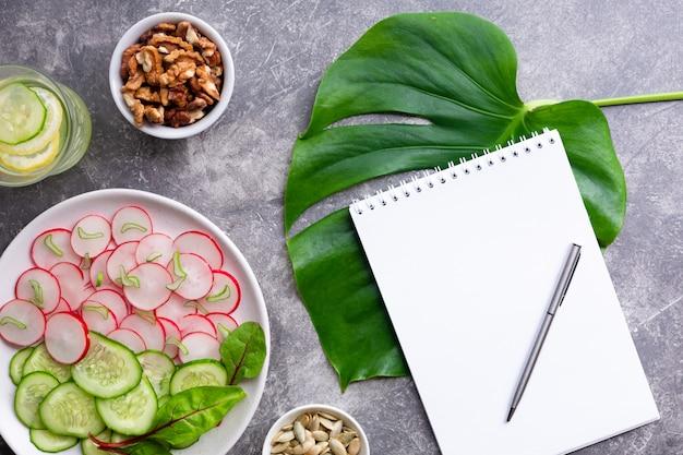 Insalata leggera di ravanello con cetriolo, bevanda disintossicante con limone, noci e semi di zucca su uno sfondo grigio.