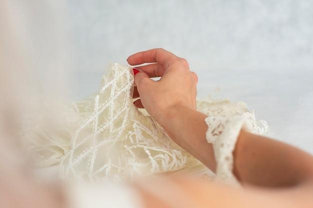 Tessuto di raso leggero con ragazza su fondo in legno con perline.
