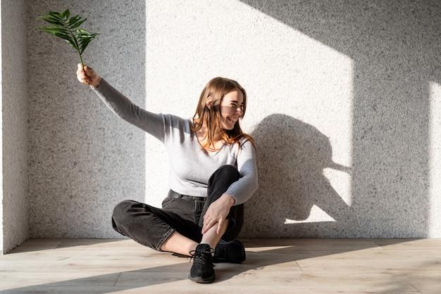 Ritratto di luci e ombre. bella giovane donna con un motivo di ombra sul viso sotto forma di foglia di palma
