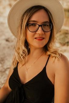 Donna dalla carnagione chiara in occhiali e un cappello sullo sfondo di una roccia di pietra.