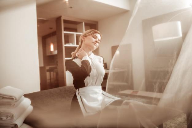 Vento estivo leggero. giovane cameriera d'albergo dai capelli biondi che si gode il leggero vento estivo dalla finestra