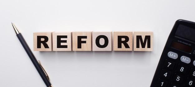Su una superficie chiara tra la calcolatrice e la penna ci sono cubi di legno con la parola reform. concetto finanziario