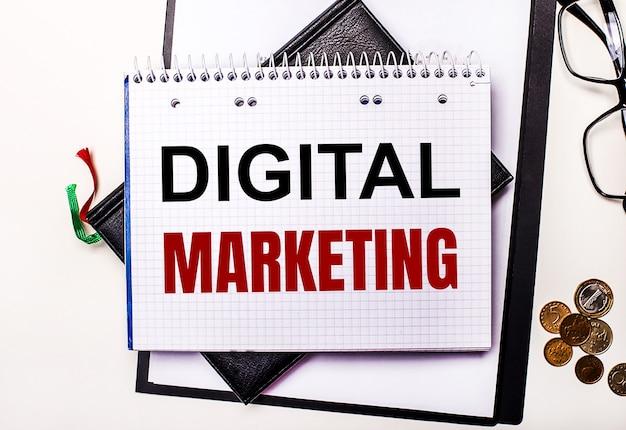Su una superficie leggera bicchieri, monete e un taccuino con la scritta digital marketing