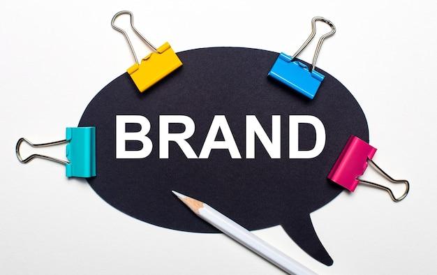 Su una superficie chiara, graffette multicolori, una matita bianca e carta nera con la scritta brand