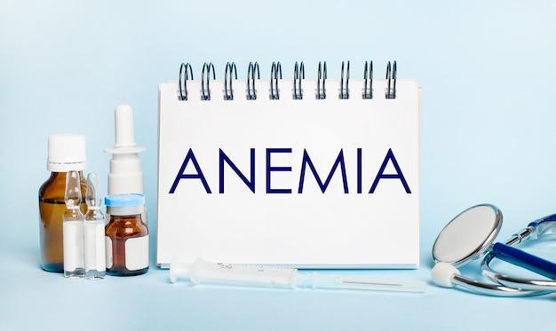 Su una superficie leggera, una siringa, uno stetoscopio, fiale di medicinale, una fiala e un blocco note bianco con il testo anemia. concetto medico