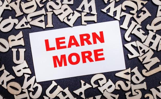 Su una superficie chiara, lettere in legno dell'alfabeto inglese e all'interno un cartoncino bianco con la scritta learn more