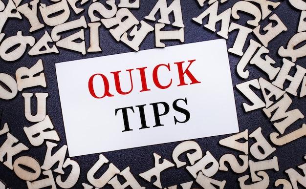 Su una superficie chiara, lettere in legno dell'alfabeto inglese e all'interno un cartoncino bianco con la scritta quick tips.