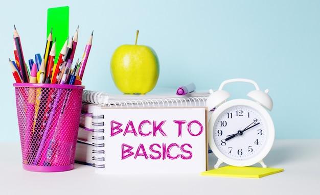 Su un tavolo luminoso ci sono libri, cancelleria, una sveglia bianca, una mela. accanto c'è un quaderno con il testo back to basics. concetto educativo.