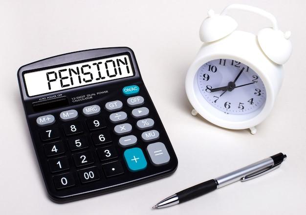 Sul tavolo luminoso c'è una calcolatrice nera con la scritta pensione sul tabellone segnapunti, una penna e una sveglia bianca. concetto di affari