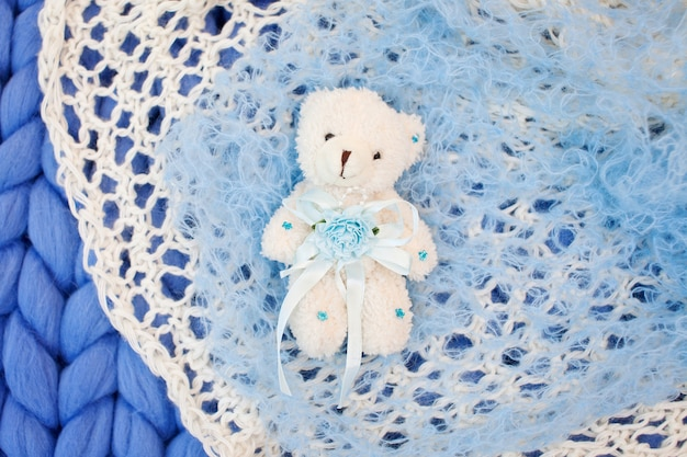 Giocattolo leggero dell'orsacchiotto su un plaid lavorato a maglia.