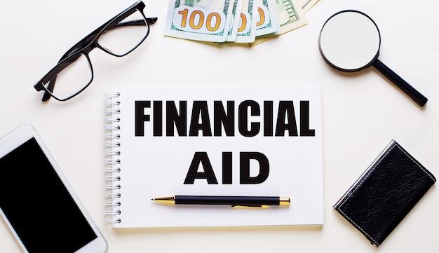 Su una parete chiara, occhiali, una lente d'ingrandimento, soldi, un telefono e un taccuino con la scritta aiuto finanziario. concetto di affari