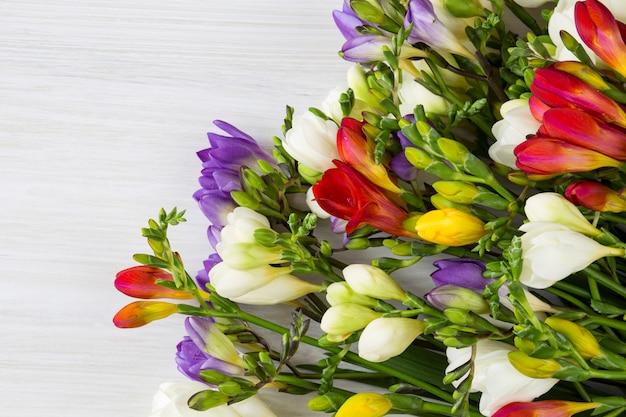 Su un fondo di legno chiaro un bouquet di fresie multicolori