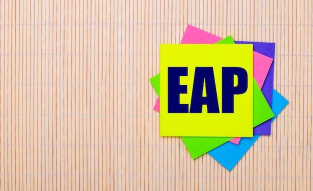 Su uno sfondo di legno chiaro, adesivi multicolori luminosi con il testo eap employee assistance program