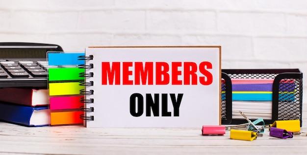Su uno sfondo di legno chiaro, una calcolatrice, bastoncini multicolori e un quaderno con il testo solo per i membri. concetto di affari
