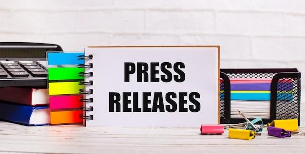 Su uno sfondo di legno chiaro, una calcolatrice, bastoncini multicolori e un quaderno con il testo comunicati stampa. concetto di affari