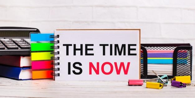 Su uno sfondo di legno chiaro, una calcolatrice, bastoncini multicolori e un quaderno con il testo il tempo è adesso. concetto di affari