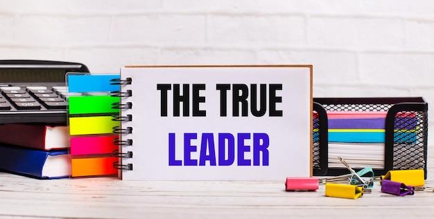 Su uno sfondo di legno chiaro, una calcolatrice, bastoncini multicolori e un quaderno con il testo il vero leader. concetto di affari